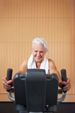 Elderly woman exercising on bicycle in a gym Stock Photo - 8209274