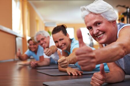 seniors laughing: Gruppo felice fitness in palestra holding loro thumbs up