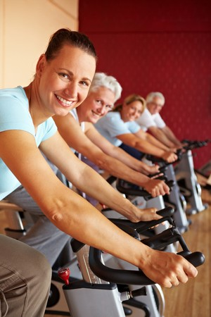 training device: People in a gym sitting on spinning bikes Stock Photo