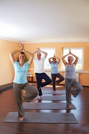 haciendo ejercicio: Grupo de yoga en un gimnasio haciendo ejercicio de Vrikshasana (The Tree)  Foto de archivo