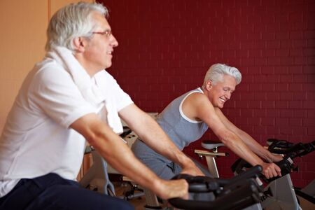 Two happy senior people on spinning bikes in gym photo