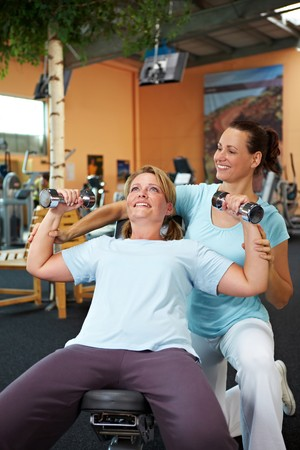 back training: Woman doing dumbbell exercises with fitness trainer in gym Stock Photo