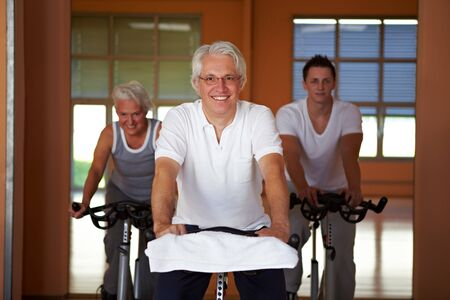 Spinning class with senior people in a gym photo
