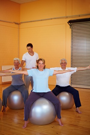 Fitness group in gym doing back exercises photo