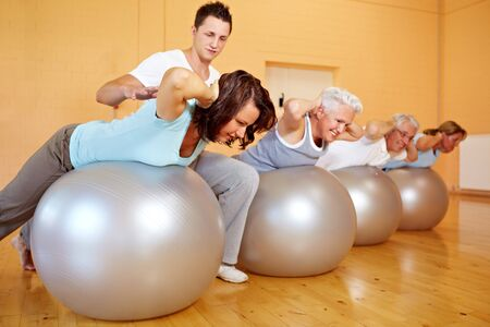 Fitness trainer in a gym teaching back exercises Stock Photo - 8209453