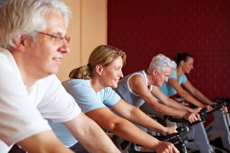 People in a gym sitting on spinning bikes photo
