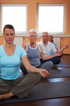 Yoga group in gym doing meditation exercises photo