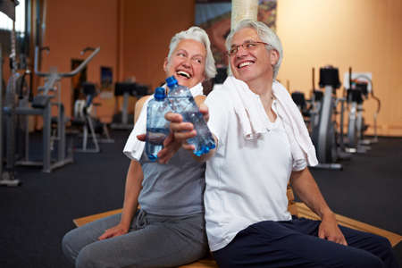 Two happy senior people in a gym drinking water photo