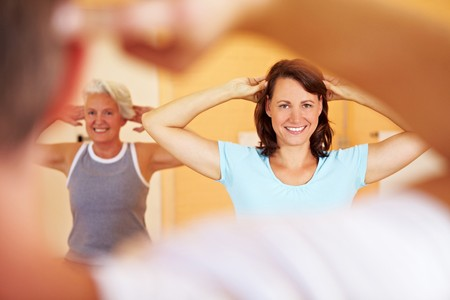 Group in a gym doing gymnastics with a fitness trainer photo