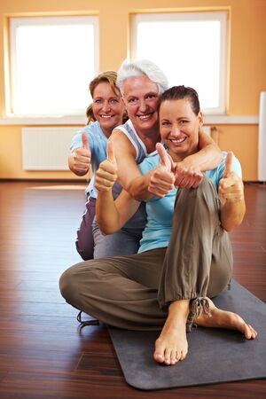 Three happy women in a gym holding their thumbs up photo
