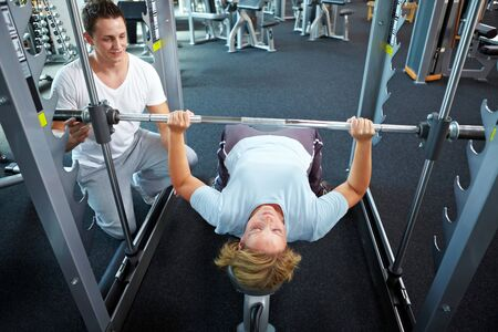 'personal beauty': Woman lifting weights with personal trainer in a gym Stock Photo