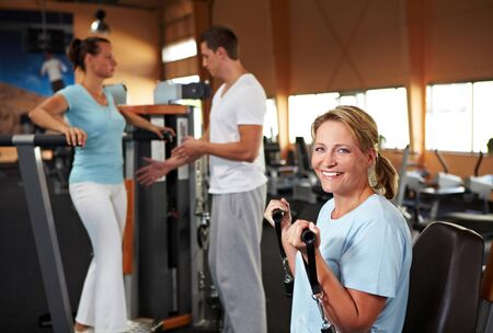 Women doing fitness exercises in a gym with fitness trainer photo