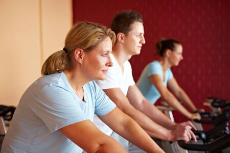 Three people working out on spinning bikes in gym photo