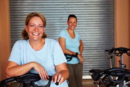 Two smiling women standing in spinning room in a gym photo