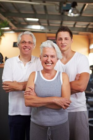 Senior people and their fitness coach in a gym photo