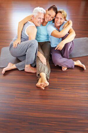 Three happy women sitting in a gym photo