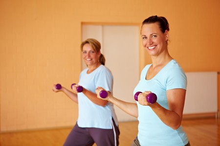 Two happy women doing dumbbell exercises in gym photo