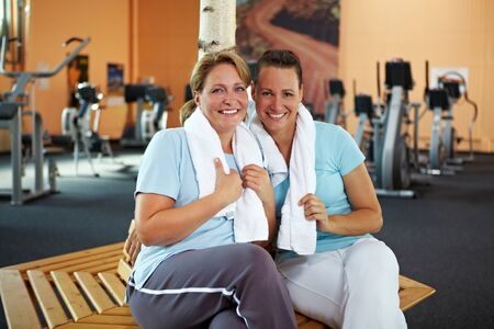 woman in towel: Two happy women talking after their fitness training in gym
