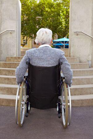 discriminacion: Anciana en silla de ruedas mirando de escaleras