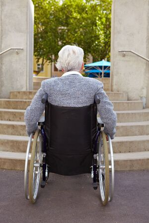 paralyzed: Elderly woman in wheelchair looking at stairs Stock Photo