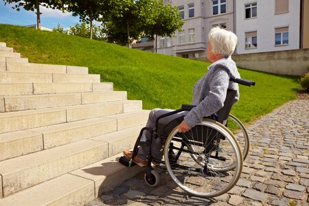 exclusion: Elderly woman in wheelchair looking at stairs Stock Photo
