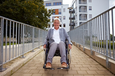 ramp: Happy elderly woman in wheelchair using a ramp Stock Photo