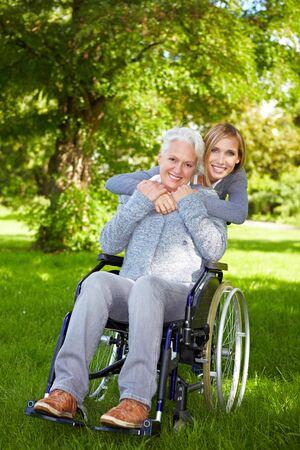 discapacidad: Mujer feliz en silla de ruedas con una mujer joven en la naturaleza