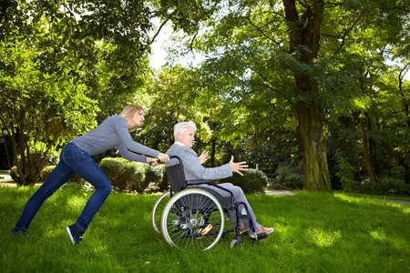 Young woman having difficulties pushing a wheelchair over a meadow Stock Photo - 8287003