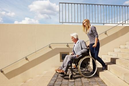 discriminacion: Joven ayudando a una anciana en silla de ruedas
