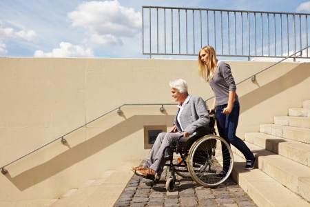 handicapped accessible: Young woman helping an elderly woman in wheelchair Stock Photo