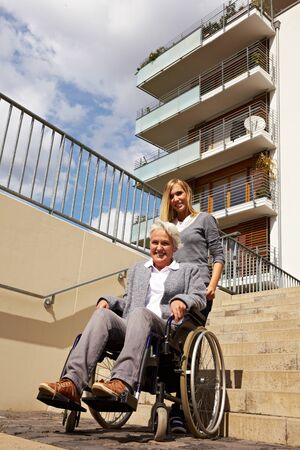 Young woman helping an elderly woman in wheelchair with staircase photo