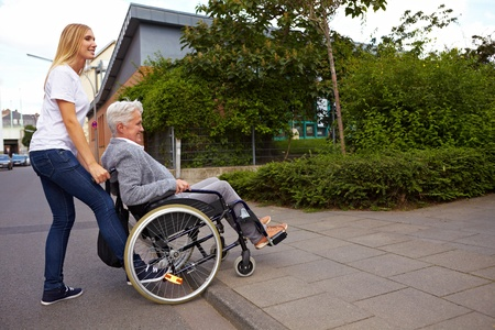 mobility nursing: Young woman helping elderly woman in wheelchair over a curbstone