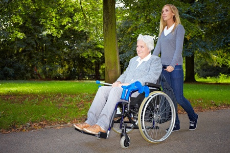 mobility nursing: Happy woman in wheelchair with young woman in nature Stock Photo