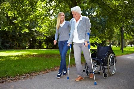 fysiotherapie: Verpleegkundige helpen bejaarde vrouw met haar fysiotherapie buitenshuis Stockfoto
