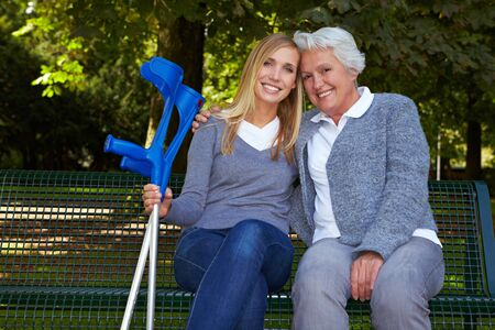 crutches: Smiling granddaughter with handicapped grandmother on park bench