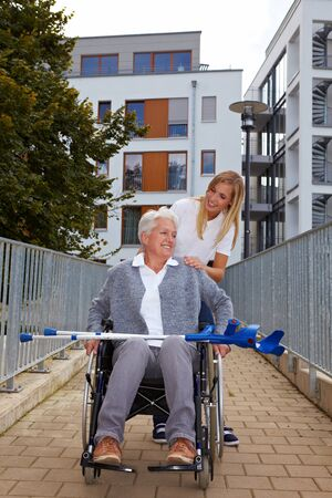 Happy woman in wheelchair with nurse on a ramp photo