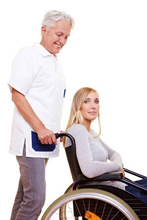mobility nursing: Nurse caring for a young woman in wheelchair Stock Photo