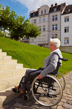 Elderly woman in wheelchair looking at stairs photo