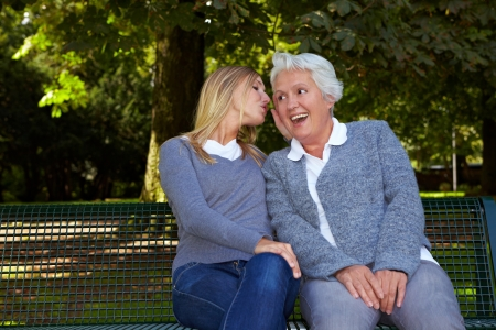 the deaf: Woman whispering her deaf grandmother in the ear
