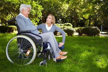 rollstuhl: Junge Krankenschwester im Gespr�ch mit Frau im Rollstuhl in park Lizenzfreie Bilder