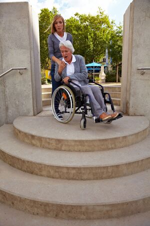 immobility: Elderly woman in wheelchair looking at inaccessible staircase Stock Photo