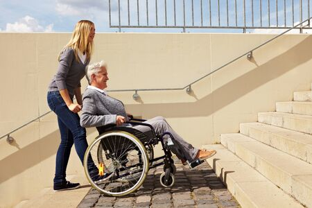 Young woman helping an elderly woman in wheelchair with staircase Stock Photo - 8287016
