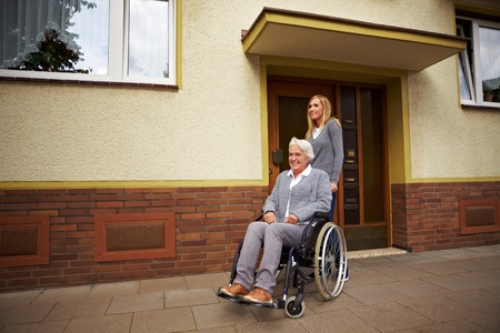 Smiling elderly woman in front of a retirement home Stock Photo - 8291719