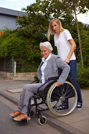 immobility: Young woman helping elderly woman in wheelchair over a curbstone