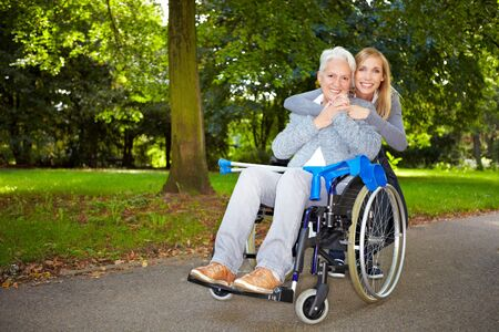 Granddaughter embracing her grandmother in wheelchair outdoors photo
