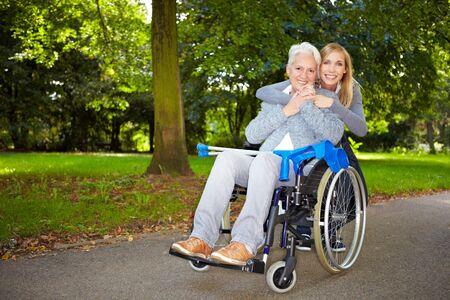 silla de ruedas: Nieta abrazando a su abuela en silla de ruedas al aire libre  Foto de archivo