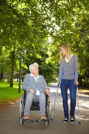 Zwei Frauen in Rollstuhl und auf Krücken sprechen in einem park Standard-Bild
