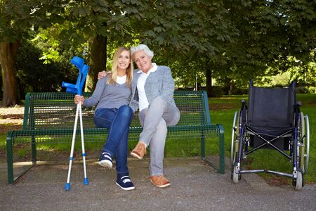 Young woman sitting with elderly handicapped woman on a park bench photo
