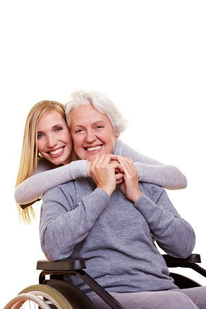 rehab: Young woman embracing disabled elderly woman in wheelchair