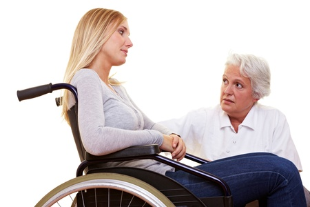 Doctor talking to young disabled woman in wheelchair photo